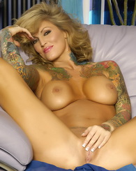 The very busty, sexy Janine Lindemulder is looking stunning as she strips down out of her sexy dress, showing off her shaved pussy and tattooed body!